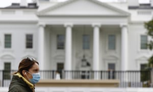 A woman wearing a face mask walks past the White House in Washington on 1 April 2020.