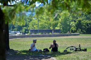 People seek shade in David Lam park in Vancouver. Residents in parts of the Lower Mainland, Victoria and the Okanagan region are reported to have been booking air-conditioned rooms so they can continue working and also get some sleep