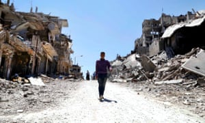 Residents arrive on foot to inspect their homes in the Wadi Al-Sayeh district at the al-Khalidiyeh area in Homs.