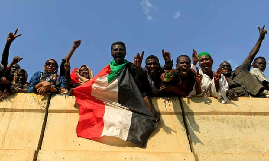 Khartoum: civilians hold their national flag as they celebrate the signing of the Sudan's power sharing deal.