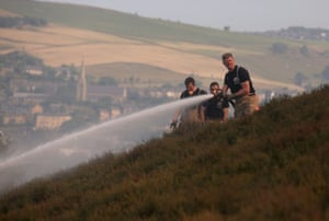 Firefighters on Saddleworth Moor attempt to dampen down the area to stop the spread of fire.