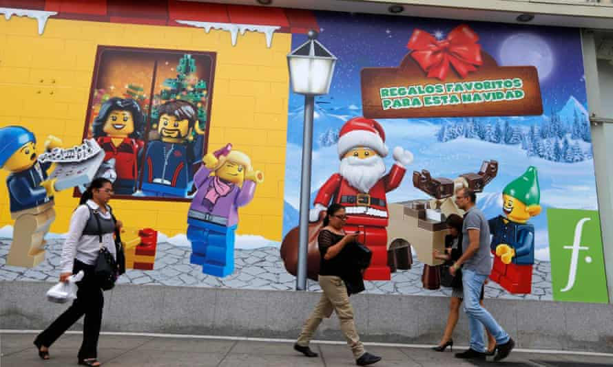 People walk past Christmas Lego display.