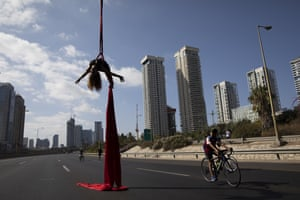 Tel Aviv, Israel. Acrobat Tel Karassin performs on a car-free highway, during the Jewish holiday of Yom Kippur. Many residents take bicycles onto the streets as no traffic is permitted on the roads