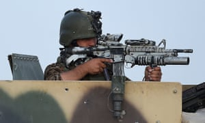 An Afghan soldier keeps watch during an ongoing battle between Taliban militants and Afghan security forces in Helmand province.