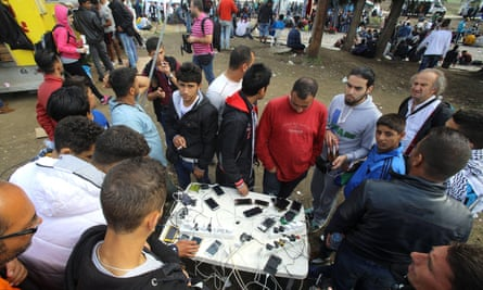 Migrants charge their phones at a UN camp in the village of Idomeni, Greece