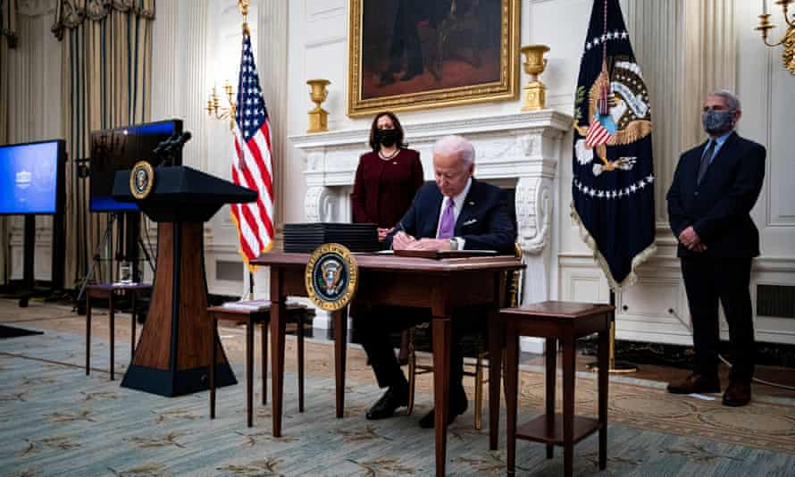 Joe Biden, flanked by Kamala Harris and Anthony Fauci, signs a series of executive orders aimed at tackling the coronavirus crisis.