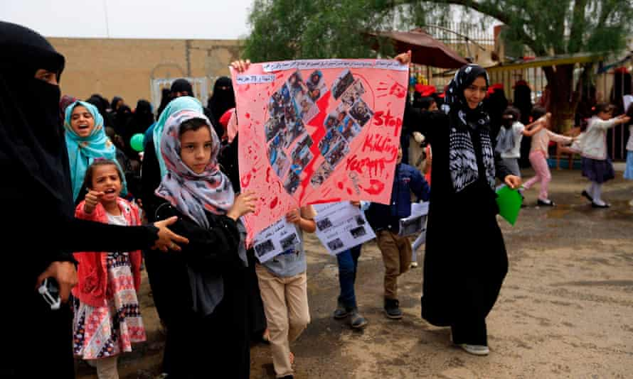 Yemeni children raise signs and chant slogans during a demonstration against the airstrike on the school bus.