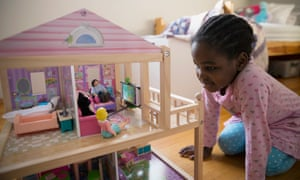Child playing with her dollhouse.
