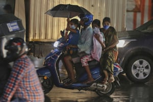 A family rides a motorcycle in the rain in Hyderabad.