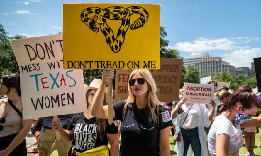 Protesters hold up signs at a protest outside the Texas state capitol on 29 May in Austin, Texas.