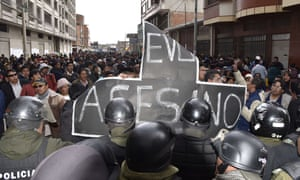 People holding at a sign reading 'Evo assassin' at a demonstration in El Alto on 17 February 2016