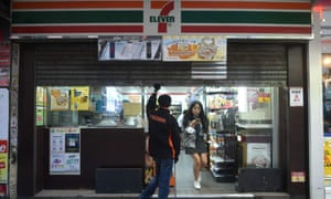 A customer leaves as an employee pulls down the shutters at a convenience store normally open 24 hours a day in Hong Kong