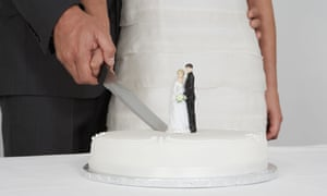 A married couple cutting a wedding cake.