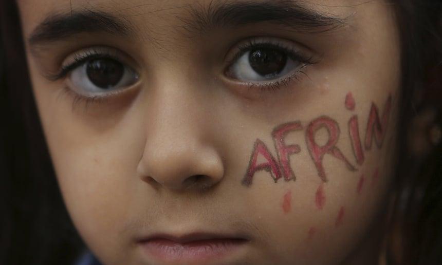 Una bambina curda che vive a Cipro con la faccia dipinta durante una protesta contro l'offensiva turca contro Afrin, in Siria, 2017. Credits to: Petros Karadjias/AP.