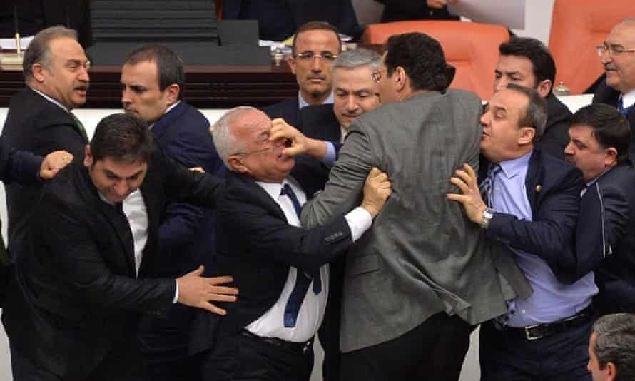 Lawmakers from the main opposition Republican People's Party (CHP) and ruling AK Party (R) scuffle during a debate on a legislation to boost police powers, at the Turkish Parliament in Ankara.<br>