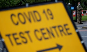 A soldier stands near a sign at the entrance of a testing centre in Blackburn
