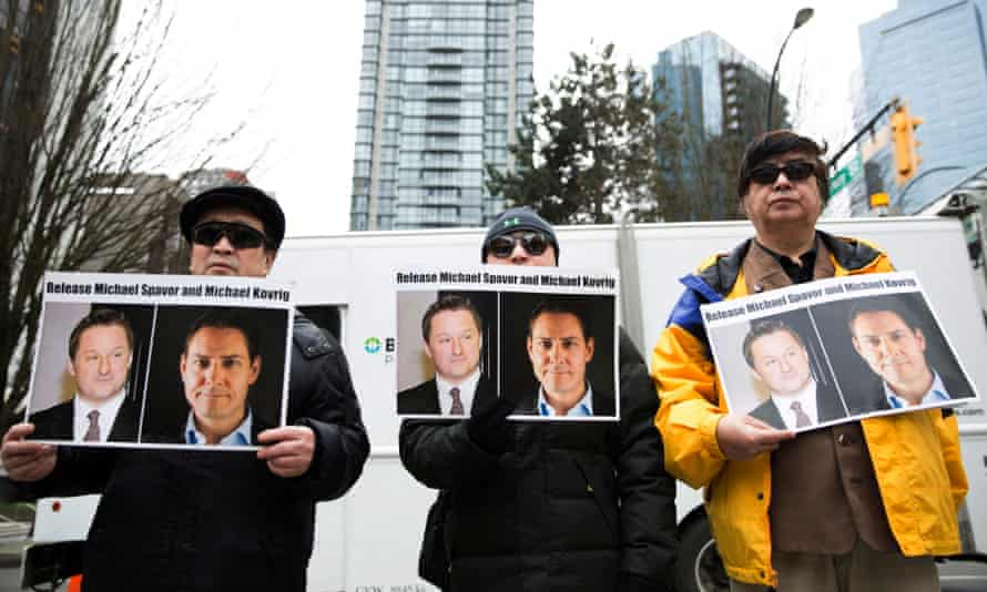 Protesters hold photos of Canadians Michael Spavor and Michael Kovrig, who are being detained by China, outside British Columbia Supreme Court, in Vancouver.