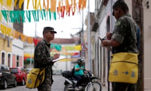 Brazilian soldiers conduct an inspection for the Aedes aegypti mosquito on a street in Recife, Brazil, on Monday.