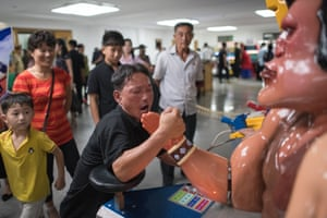 A man plays an arm wrestling game in the amusement arcade at Kaeson Youth Park.