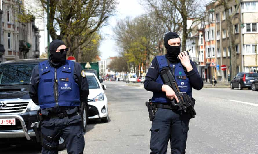 Belgian police officers stand guard in a street in Etterbeek, Brussels