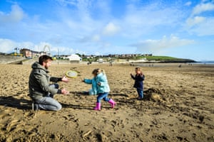 Barry Island, UKJon Wilks and his daughters, 2-year-old Maisie (centre) and 2-year-old Elen (right), from Newport, enjoy a game of frizbee and building sandcastles on the sandy beach at Barry Island, where clear skies and bright sunshine dominate the South Wales coastline as December temperatures continue to be mild.