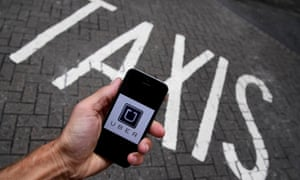the Uber app logo displayed on a mobile phone as it is held up above a taxi sign