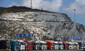 Cargo trucks wait to embark ferries in front of the white cliffs at the port of Dover