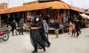 Iranians, some wearing protective equipment, walk past shops in the south-eastern city of Kerman
