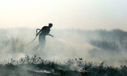 A firefighter battles a moorland blaze on Winter Hill near Rivington in Lancashire, north-west England