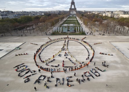 """Environmentalist activists form a human chain representing the peace sign and the spelling out """"100% renewable"""", on the side line of the Paris climate talks, 2015."""