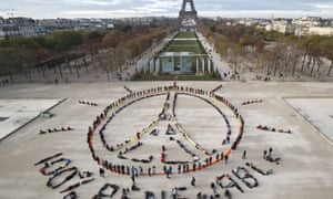 Environmental activists form a human chain to make the peace sign and spell out '100% renewable' at last year's UN climate change talks in Paris.