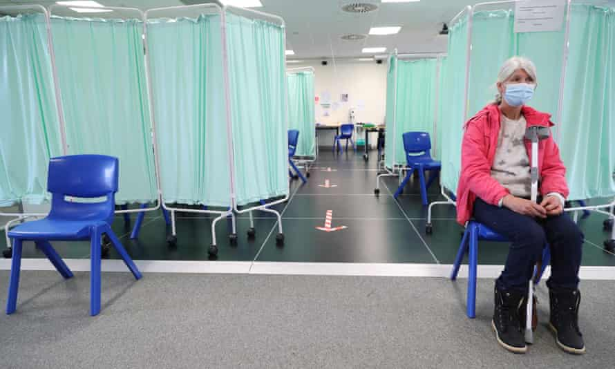 Woman waits in vaccination centre in Llanelli, south Wales