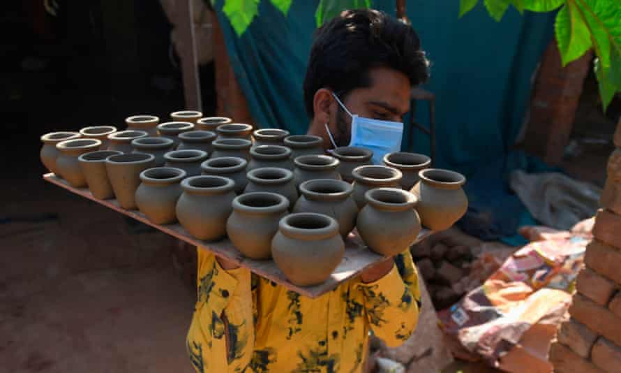 Potter Anilbhai Prajapati carries a tray of tea cups to be dried at a village workshop
