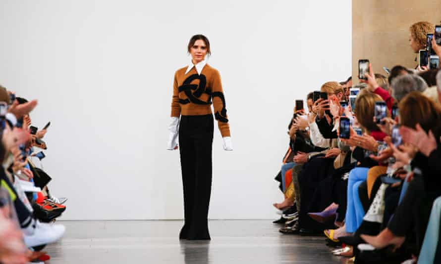 Victoria Beckham poses for photos on a catwalk