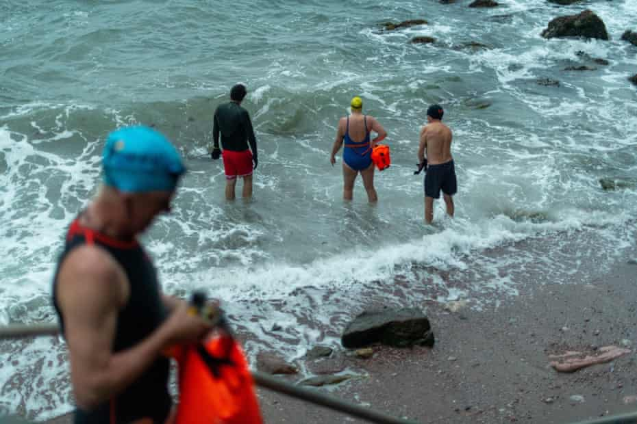 Members of the Torquay Shoal Outdoor Swimming group, taking to the water at Antsey's Cove, Torquay, Devon., on the longest day of the year.
