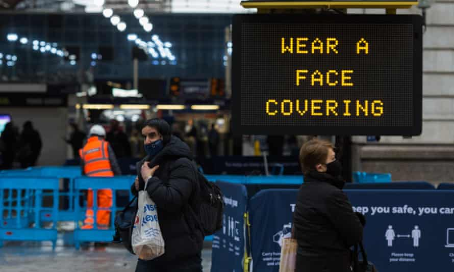 Pedestrians walk past a 'Wear a face covering' message displayed outside Victoria Station