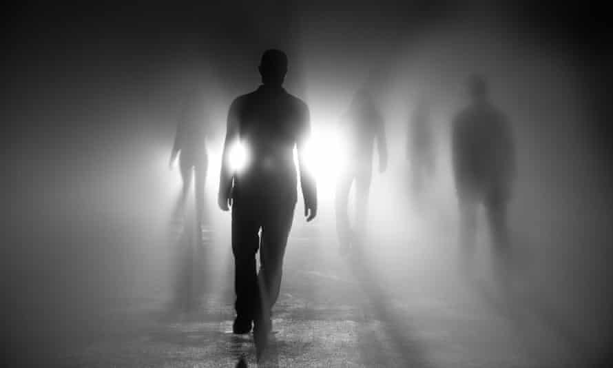 Silhouettes of people walking into light.