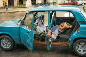 A man lies down for a siesta in blue Lada in Havana.