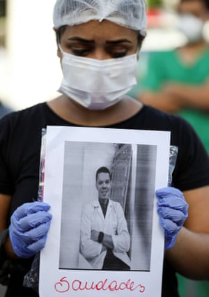 A healthcare worker wearing a protective face mask pays tribute to co-workers that have died from Covid-19 in front of the 28 de Agosto hospital in Manaus, on Monday. The sign reads: 'Miss you.'