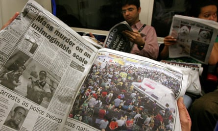 Commuters reading newspapers on a London underground train in pre-Covid times