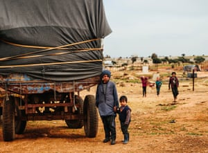 A young boy and his brother stand next to a truck at a makeshift reservation near the Syria-Turkey border.