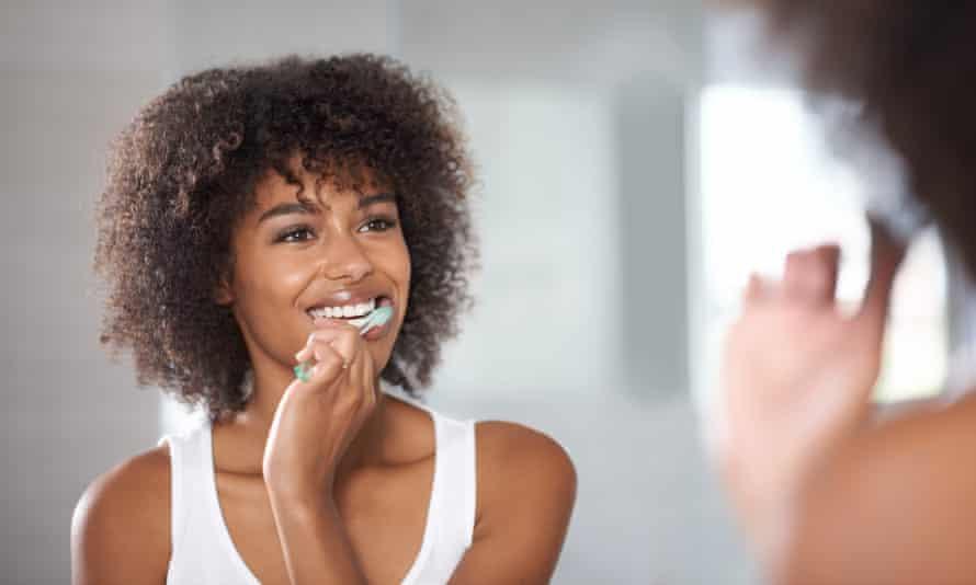Young woman brushing teeth in mirror