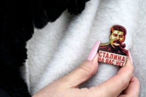 A Russian Communist party supporter adjusts a pin with an image of the Soviet leader Joseph Stalin