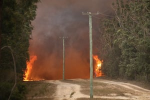 Flames race along the Sussex Inlet road south of Nowra , NSW.