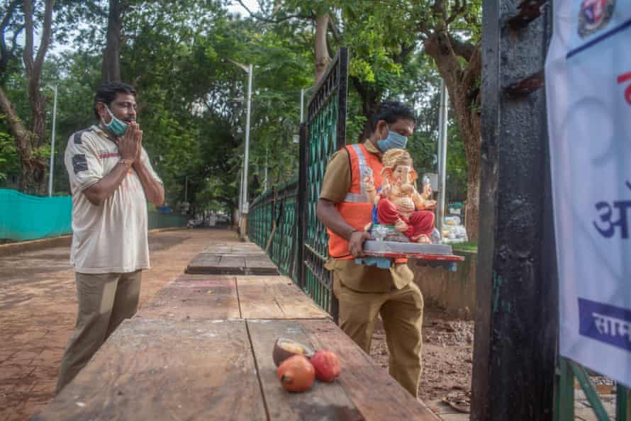 A devotee pays tribute and prays to a statue of Lord Ganesh.