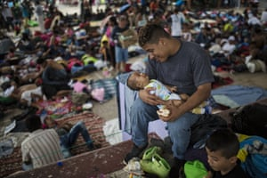 Jose Luis Ramos, a Honduran migrant traveling to the U.S. with a caravan, plays with his 3-month-old son Froilan in the central square of Mapastepec, Mexico, Wednesday, Oct. 24, 2018.