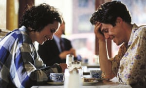 Andie MacDowell and Hugh Grant sitting at a diner table, heads bowed and laughing