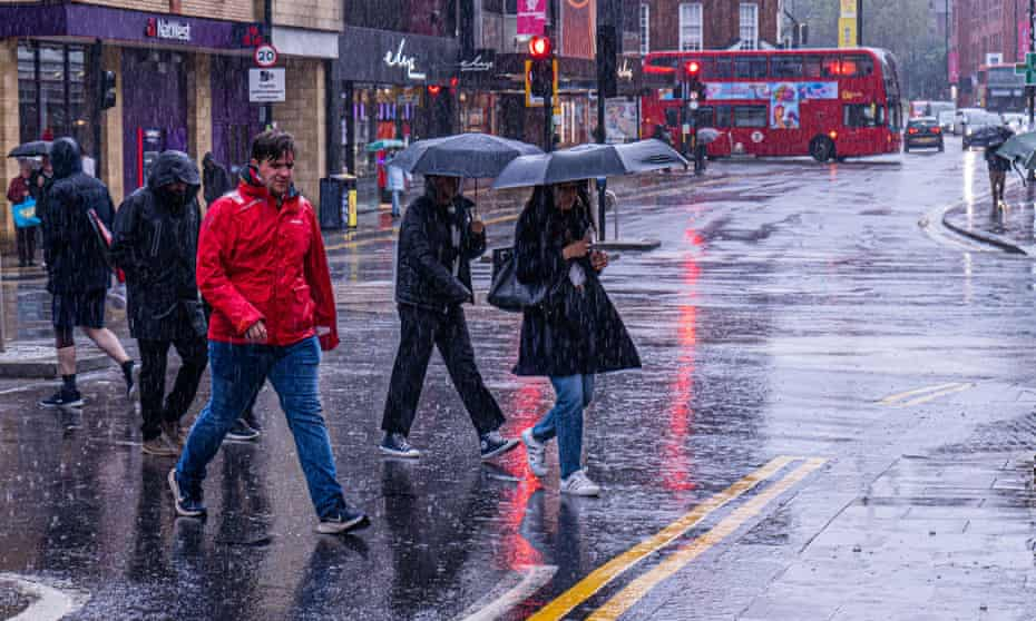 Pedestrians in Wimbledon, south-west London, during a heavy downpour on Saturday