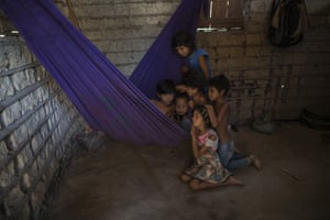 """Siblings and cousins gather around a cellphone on a purple hammock to watch a children's cartoon on YouTube, in the home of Gleison Tembe in the village Ka 'a kyr, Para state, Brazil, Monday. """"The Amazon, nature, is my mother, because it raised me. The animals that it takes care of give us strength. My children only eat natural food and it all comes here from the forest, Gleison Tembe. """"So, why deforest?"""""""