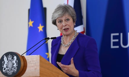 Prime minister gesticulates in front of a microphone, with European flag behind her